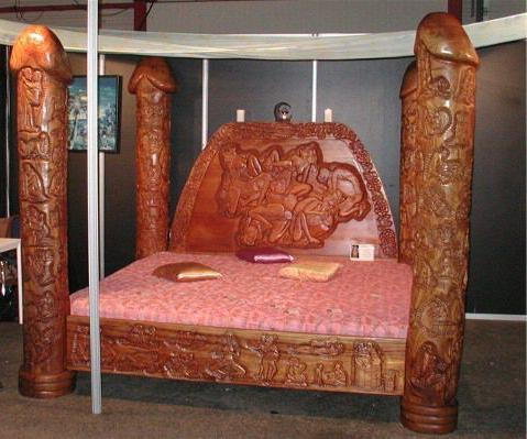 Intricate bed posts are hand carved as phalics.