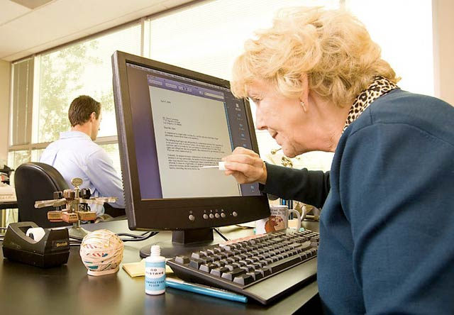 Funny photo of an older woman painting white-out on a computer screen.